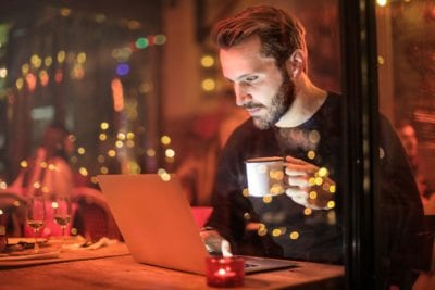 man sitting in front of computer with mug in hand image