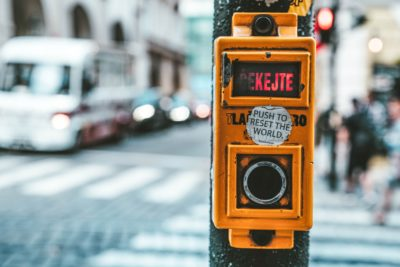 """street crosswalk button with sticker saying """"press to reset the world"""""""