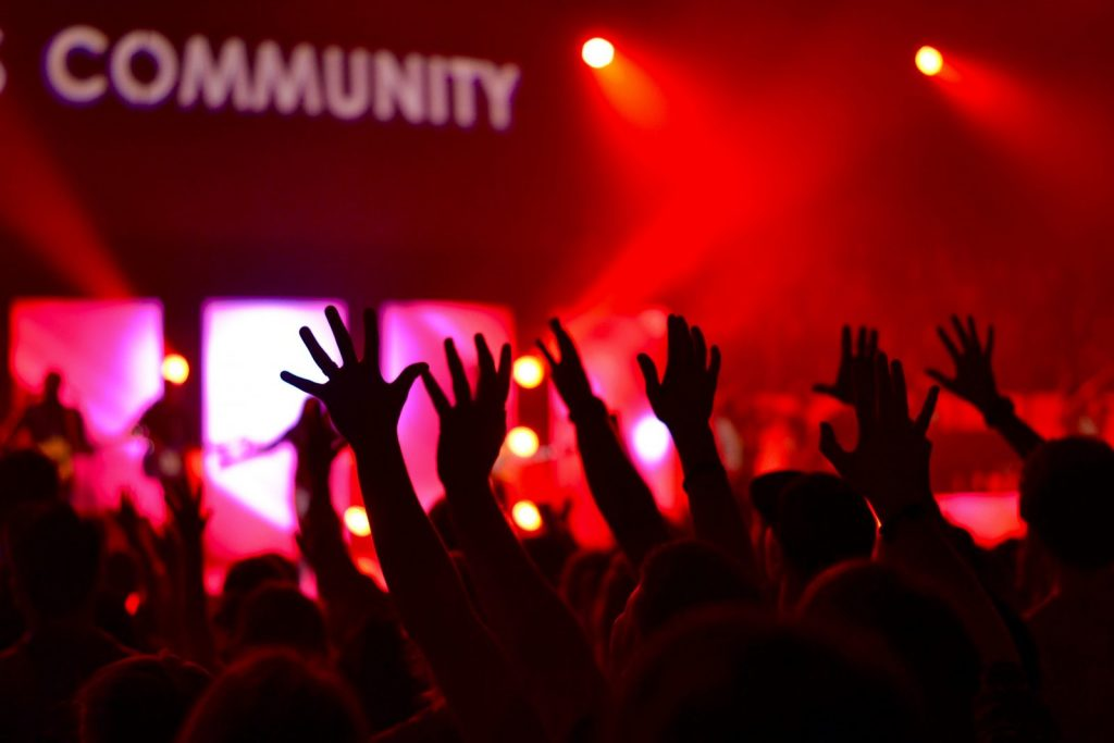 church community worship light show hands lifted